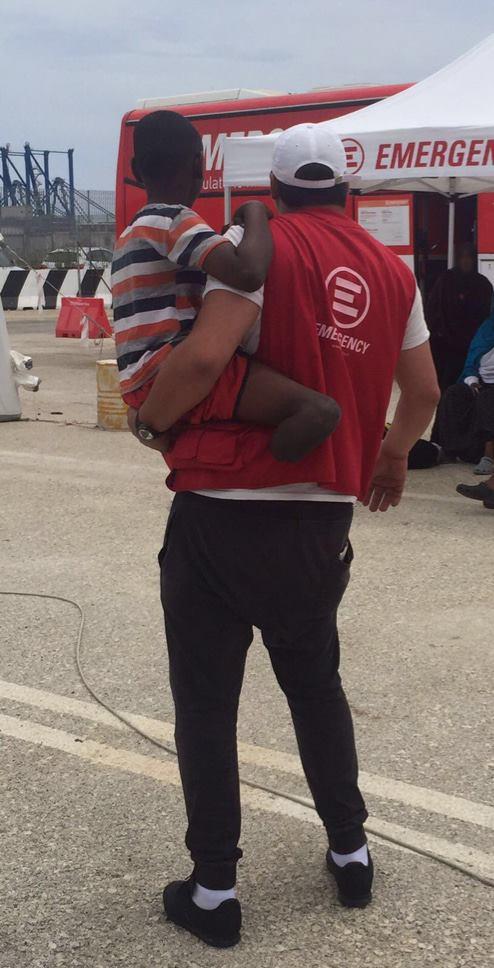 Al porto di Augusta, Bader - mediatore culturale di EMERGENCY - tiene in braccio S., un bambino arrivato dalla Somalia