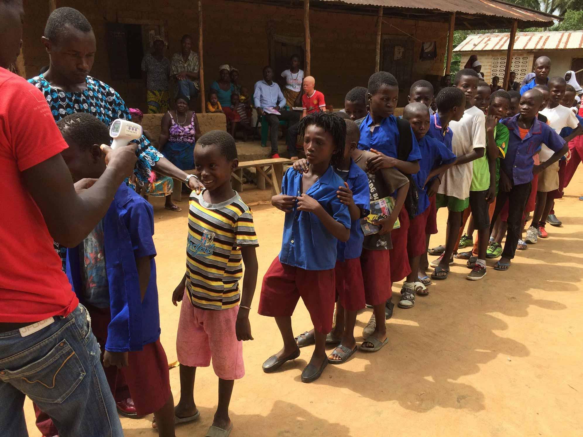 """In Sierra Leone, uno degli """"health promoter"""" di EMERGENCY misura la febbre ai bambini di un villaggio"""