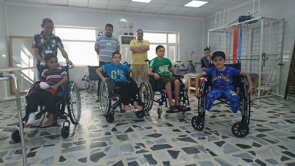 Rayyan, Abdul, Bakir, un altro bambino e i loro genitori nella sala fisioterapia del Centro di riabilitazione a Sulaimaniya