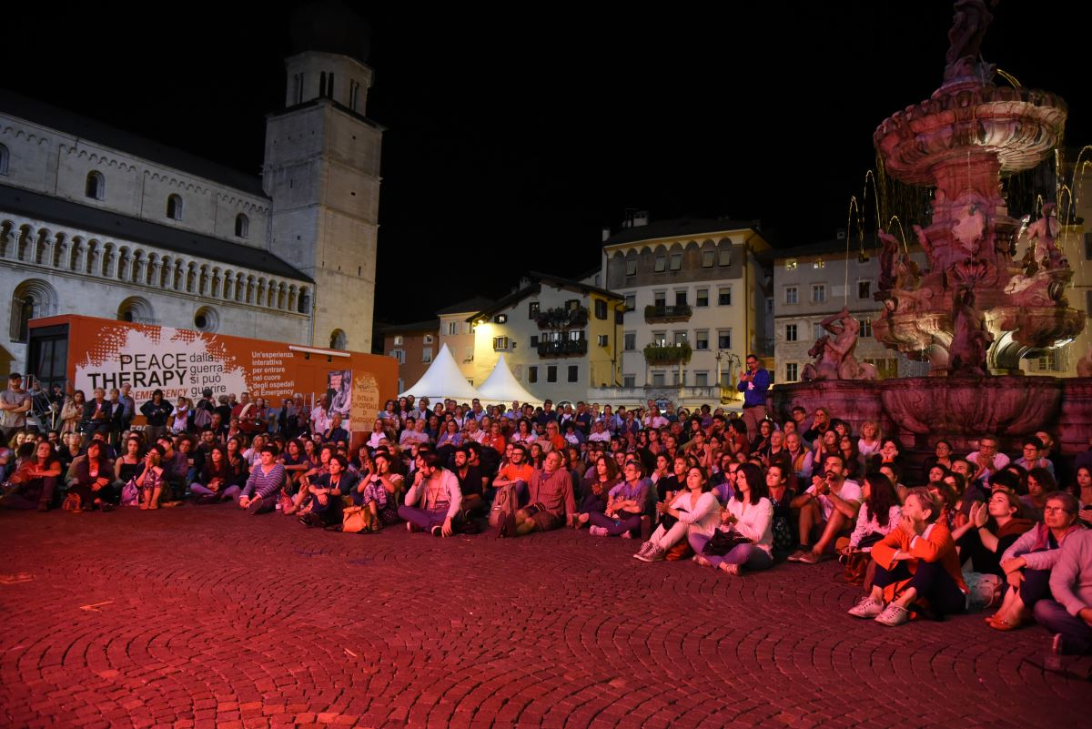 Il pubblico in piazza durante guarda la trasmissione in diretta di una conferenza